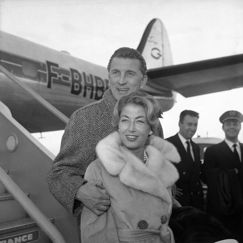 "Hollywood's Kirk Douglas and his wife Anne Douglas, formally Anne Buydens arrive at London Airport on Dec. 5, 1960, from Paris. They have flown over for the premiere of Douglas' film ""Spartacus"" at the Metropole cinema, London on Wednesday in evening. Douglas stars in the movie with Jean Simmons, unseen. (AP Photo)"