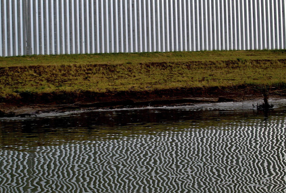 """FILE - In this Monday, April 5, 2021, file photo, the reflection of a private border wall is seen on the glassy waters of the Rio Grande on Monday, April 5, 2021, in Mission, Texas. The Biden administration said Friday it will begin work to address risks of flooding and soil erosion from the unfinished wall on the U.S. border with Mexico and provided some answers on how it will use unspent money from shutting down one of President Donald Trump's signature domestic projects. Construction under the Trump administration """"blew large holes"""" into the flood barrier system of low-lying regions in Texas' Rio Grande Valley, the Homeland Security Department said. It said it will """"quickly repair"""" the flood barrier system without extending the wall. Hidalgo County, Texas, officials have expressed alarm about flooding risks during the hurricane season starting in June from breaches in a levee system after Biden halted border wall construction immediately after taking office in January. (Delcia Lopez/The Monitor via AP, File)"""