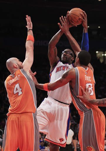 New York Knicks' Amare Stoudemire, center, shoots over Phoenix Suns' Marcin Gortat (4) and Channing Frye (8) during the first half of an NBA basketball game on Wednesday, Jan. 18, 2012, in New York. (AP Photo/Frank Franklin II)