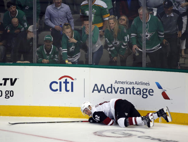 Arizona Coyotes defenseman Jordan Oesterle (82) grimaces on the ice after a hit by Dallas Stars center Tyler Pitlick during the second period of an NHL hockey game in Dallas, Thursday, Oct. 4, 2018. (AP Photo/Michael Ainsworth)