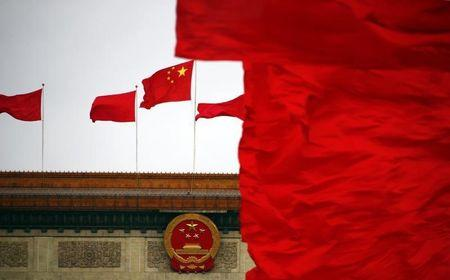 Red flags flutter next to a national emblem and a national flag of China on top of the Great Hall of the People, which is the venue of the closing ceremony of the CPPCC, in Beijing