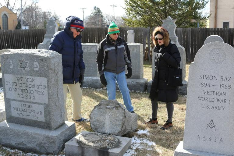 (L-R) Richard Markus, Sidney Markus (C)and Sandy Rosenthal look at a vandalized gravestone at Stone Road or Waad Hakolel Cemetery in Rochester, New York on March 3, 2017