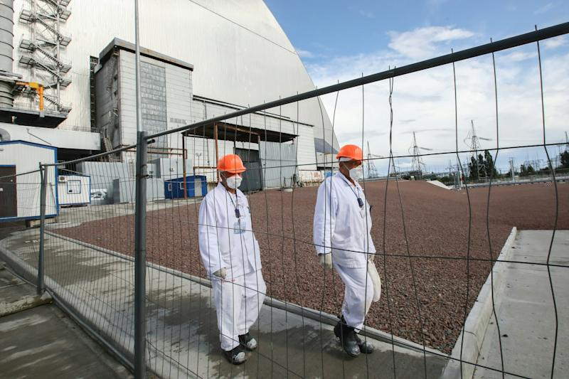 PRIPYAT, UKRAINE - JULY 10, 2019: Workers outside the new mobile metal structure, officially known as the New Safe Confinement, built over Reactor 4 of the Chernobyl Nuclear Power Plant, the new metal shelter has been officially handed over by the EU to the Ukrainian authorities; the construction of the 1.5bn euro metal shelter began in 2012; Reactor 4 is the site of the 1986 Chernobyl disaster. Pyotr Sivkov/TASS (Photo by Pyotr Sivkov\TASS via Getty Images)