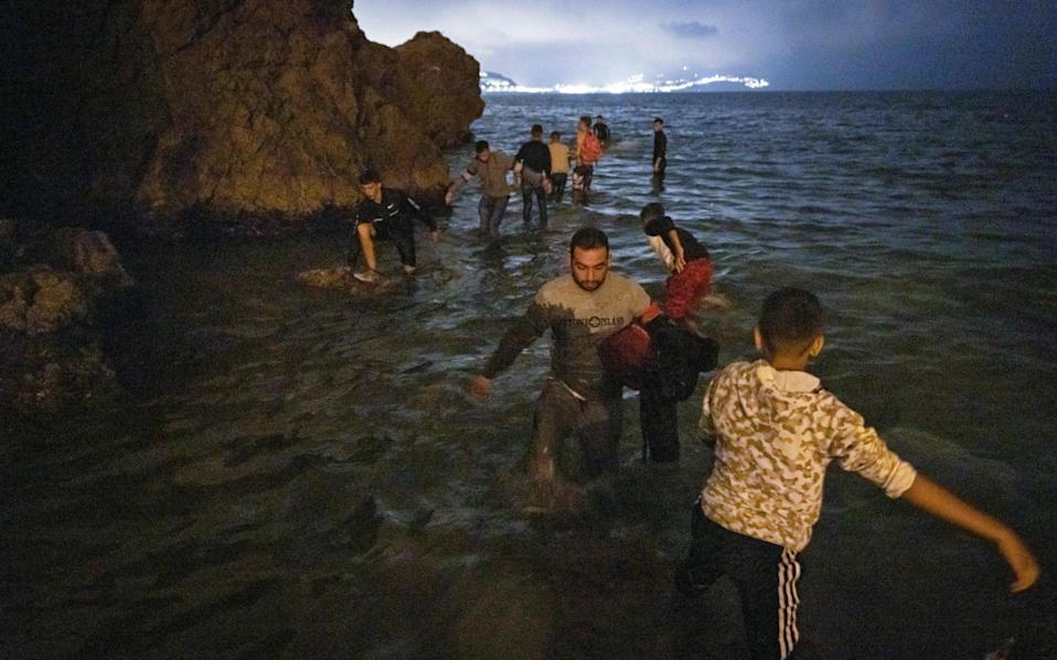 Migrants walk into shallow waters on the shore of the northern town of Fnideq - AFP/ Fadel Senna