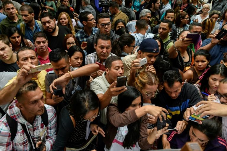 Venezuelans push and shove outside the Chilean  consulate seeking information on how to get a new visa to live in Chile