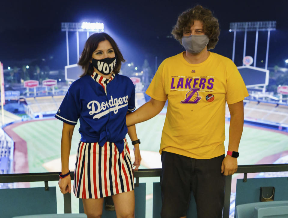 Megan Stine-Galagan, left, and Brendan Pasquini take their picture after casting their ballots in-person at the Top of the Park at Dodger Stadium in Los Angeles, Monday, Nov. 2, 2020. Turnout has been heavy during the early voting period as Californians cast ballots for president, the state Legislature, local offices and on a dozen statewide propositions. By Monday, more than 11 million people had already returned their ballots. (AP Photo/Damian Dovarganes)