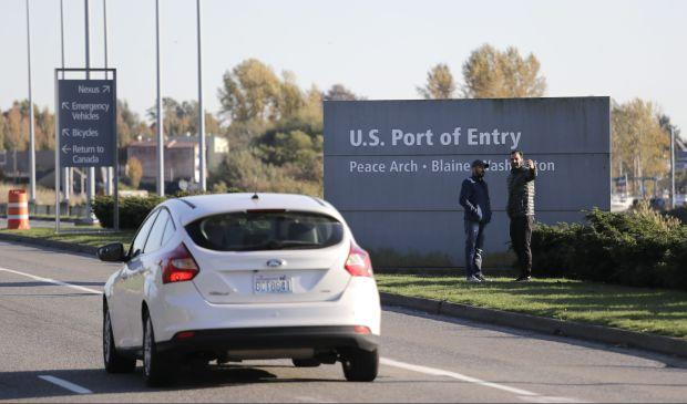 In this photo taken Oct. 9, 2019, two pedestrians take a photo at an entry sign as traffic enters the United States from Canada at the Peace Arch Border Crossing, in Blaine, Wash.