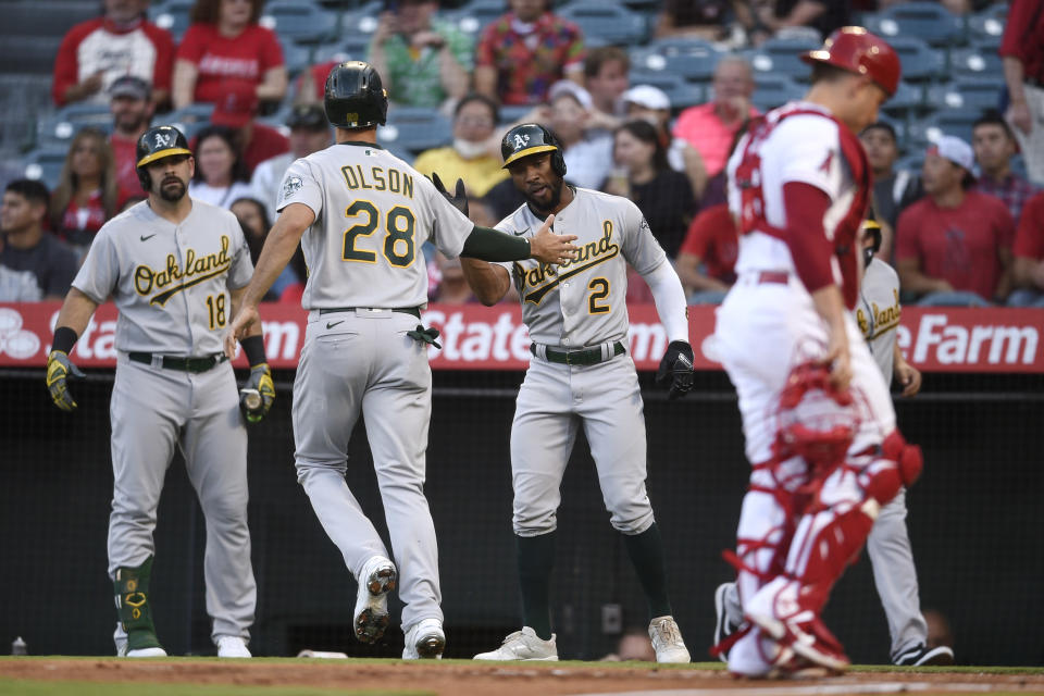 Oakland Athletics' Matt Olson, second from left, is congratulated by Mitch Moreland, left, and Starling Marte after Marte and Olson scored on a ground rule double by Ramon Laureano during the first inning of a baseball game against the Los Angeles Angels in Anaheim, Calif., Thursday, July 29, 2021. (AP Photo/Kelvin Kuo)