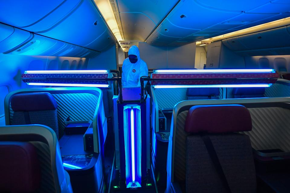 An employee of the Chilean-Brazilian airline LATAM monitors the operation of an autonomous robot that uses type C ultraviolet light (UV-C) to clean the interior of the aircraft, amid the novel coronavirus COVID-19 pandemic, at Guarulhos International Airport, near Sao Paulo, Brazil, on November 20, 2020. - Developed by LATAM engineers, this method, combined with other hygiene procedures, eliminates up to 99.9% of viruses and bacteria on board, according to the company. (Photo by Nelson ALMEIDA / AFP) (Photo by NELSON ALMEIDA/AFP via Getty Images)