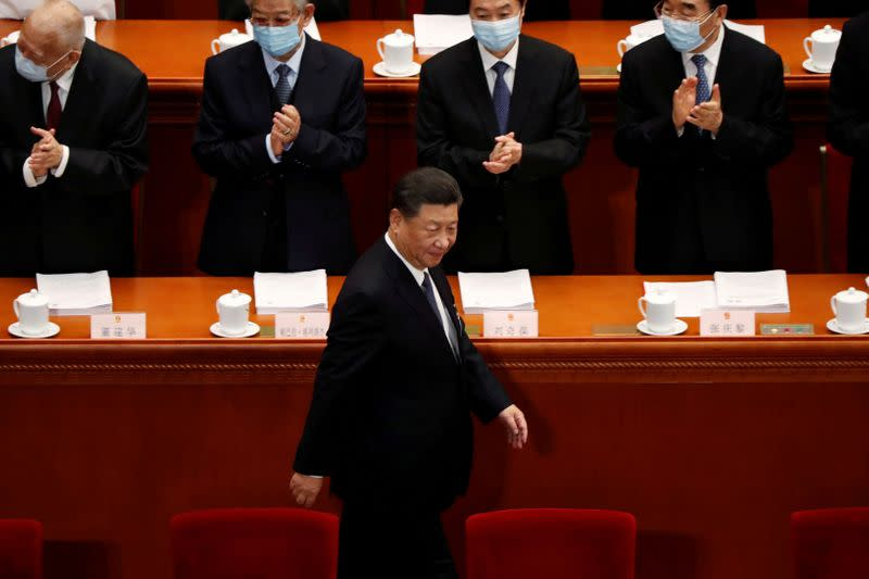 FILE PHOTO: Chinese President Xi Jinping walks past officials wearing face masks following the coronavirus disease (COVID-19) outbreak as he arrives for the opening session of the National People's Congress (NPC) at the Great Hall of the People in Beijing