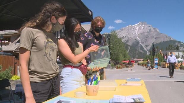 Luna Kawano, centre, displays one of Banff Isn't Disposable's reusable takeout containers. (Helen Pike/CBC - image credit)