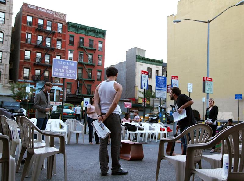 "This July 29, 2013 photo shows actors rehearsing for ""Richard III"" in a parking lot in New York. Acting in one of Shakespeare's plays is difficult enough without having to dodge a 3,600-pound SUV. The bare-boned but enthusiastic summer production has as many as 77 plastic chairs that are placed in rows around a section of concrete that acts as the stage. If a car needs to get in or out, the actors pause and the patrons pick up their seats and make room. (AP Photo/Mark Kennedy)"