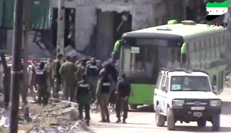 "In this image made from amateur video released by Ugarit News, which has been authenticated based on its contents and other AP reporting, Syrian rebels board a bus to leave Homs, Syria, Wednesday, May 7, 2014. Exhausted and worn out from a year-long siege, hundreds of Syrian rebels on Wednesday left their last remaining bastions in the heart of the central city of Homs under a cease-fire deal with government forces. The exit of some 1,200 fighters and civilians will mark a de facto end of the rebellion in the battered city, which was one of the first places to rise up against President Bashar Assad's rule, earning it the nickname of ""capital of the revolution.""(AP Photo/Ugarit News via AP Video)"