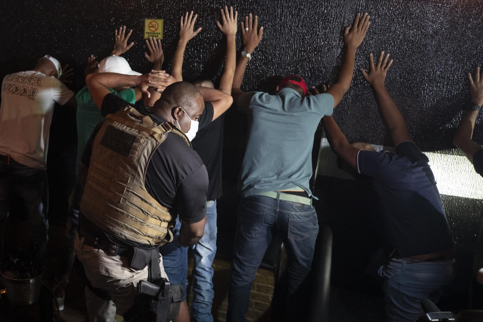 A policeman frisks people in a night club during a police operation against illegal and clandestine gatherings that authorities believe are partly responsible for fuelling the spread of COVID-19, in Sao Paulo, Brazil, early Sunday, April 11, 2021. (AP Photo/Andre Penner)