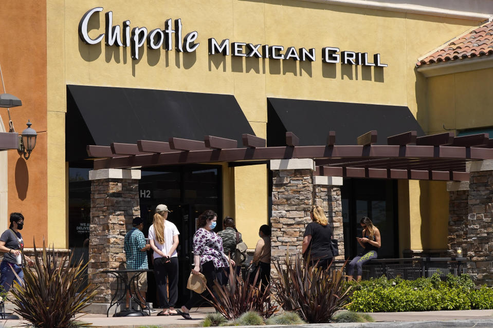 People wait outside a Chipotle Mexican Grill restaurant at the Simi Valley Town Center, Tuesday, April 21, 2020, in Simi Valley, Calif. Federal prosecutors say Chipotle Mexican Grill has agreed to pay a record $25 million fine to resolve criminal charges that it served tainted food that sickened more than 1,100 people in the U.S. from 2015 to 2018. The fast food company was charged Tuesday in Los Angeles federal court with two counts of violating the Food, Drug, and Cosmetic Act by serving adulterated food. The charges stem from outbreaks of norovirus, which causes diarrhea, at Chipotle restaurants. The virus is easily transmitted by infected food food workers. The Newport Beach, California-based company will avoid conviction by improving its food safety. (AP Photo/Mark J. Terrill)