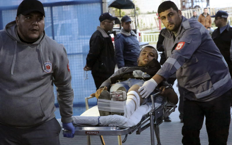 Medics move a wounded youth, who was shot by Israeli troops during a protest at the Gaza Strip's border with Israel, into the treatment room of Shifa hospital in Gaza City, Friday, April 5, 2019. Thousands of Palestinians thronged to the perimeter fence between Israel and the Hamas-ruled Gaza Strip Friday for a protest as the weekly event entered a second year. (AP Photo/Adel Hana)
