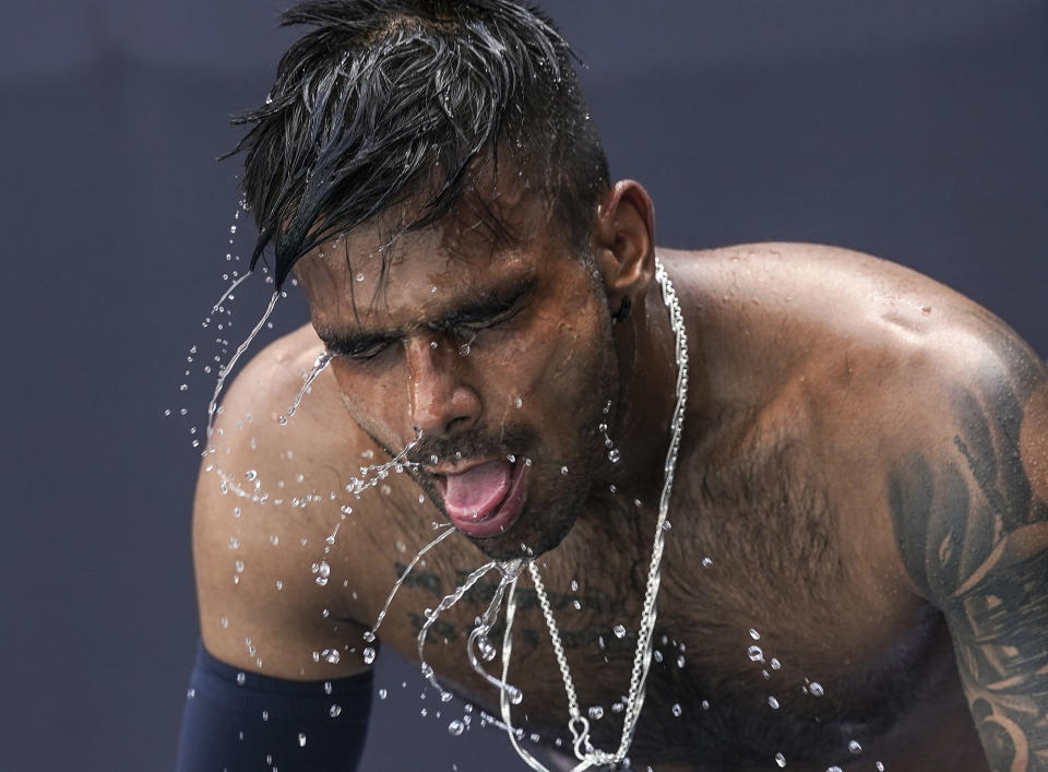 <p>India's Sumit Nagal shakes water off after pouring water on his head to cool down during a heat break while playing a qualifying match against Uzbekistan's Denis Istomin during the first round of the Tennis competition of the Tokyo 2020 Olympic Games at Ariake Tennis Park on Saturday, July 24. 2021. (Photo by Toni L. Sandys/The Washington Post via Getty Images)</p>