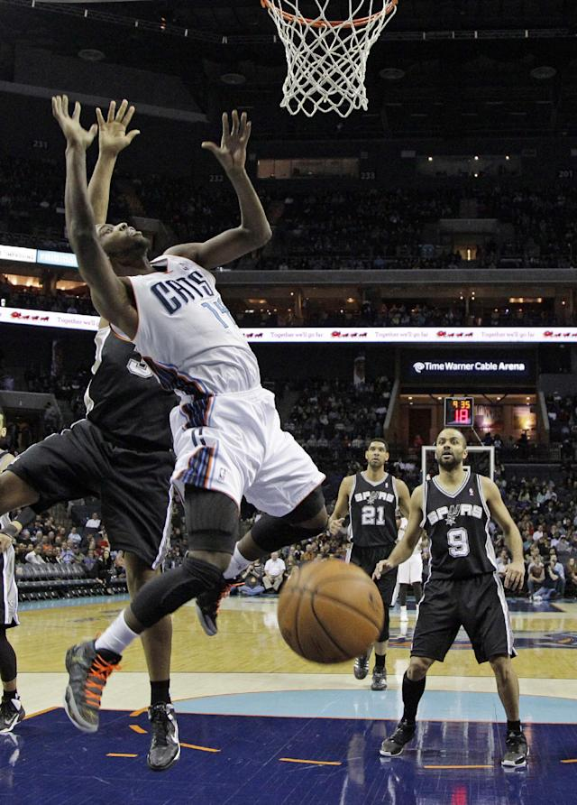Charlotte Bobcats' Michael Kidd-Gilchrist, center, is fouled by San Antonio Spurs' Boris Diaw, back left, during the first half of an NBA basketball game in Charlotte, N.C., Saturday, Feb. 8, 2014. (AP Photo/Chuck Burton)