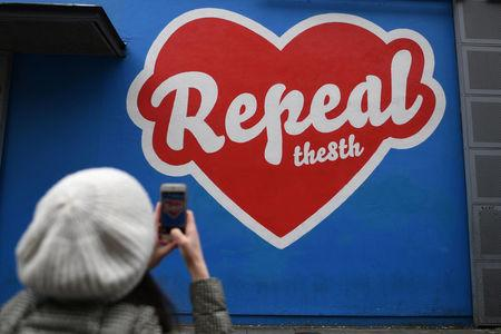 A woman takes a picture of a pro-choice mural ahead of a 25th May referendum on abortion law in Dublin, Ireland, April 12, 2018. REUTERS/Clodagh Kilcoyne