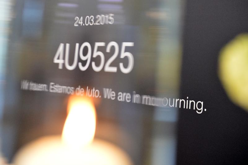A candle is lit in front of a board with the flight number of Germanwings plane 4U92524 and the lettering 'We are in mourning' in English, German and Spanish at the Congress Center in Hamburg, on April 29, 2015 (AFP Photo/Carmen Jaspersen)