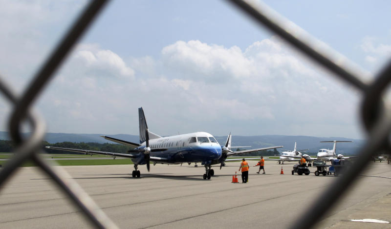 In an Aug. 9, 2011 photo, ground crew works on a flight at the Morgantown Municipal Airport in Morgantown, W.Va. The fight over subsidies to rural air carriers was a key sticking point that led to the recent political standoff in Washington that temporarily shut down the Federal Aviation Administration, putting thousands out of work. The subsidy, called the Essential Air Program, was created when airlines were deregulated in 1978 to ensure continued service on less-profitable routes to remote communities. The Essential Air Service program costs $200 million out of the roughly $3.7 trillion federal budget.  (AP Photo/Vicki Smith)