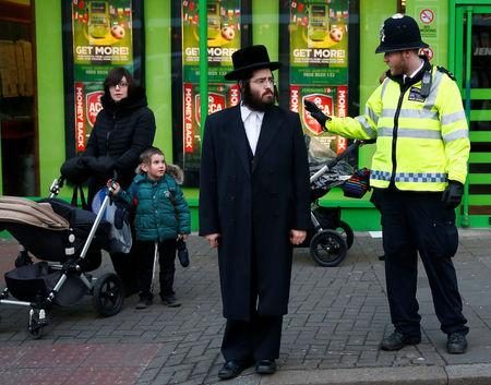 FILE PHOTO: A police officer waves to a child as members of the Jewish community wait to cross a road in north London January 20, 2015. REUTERS/Andrew Winning/File Photo