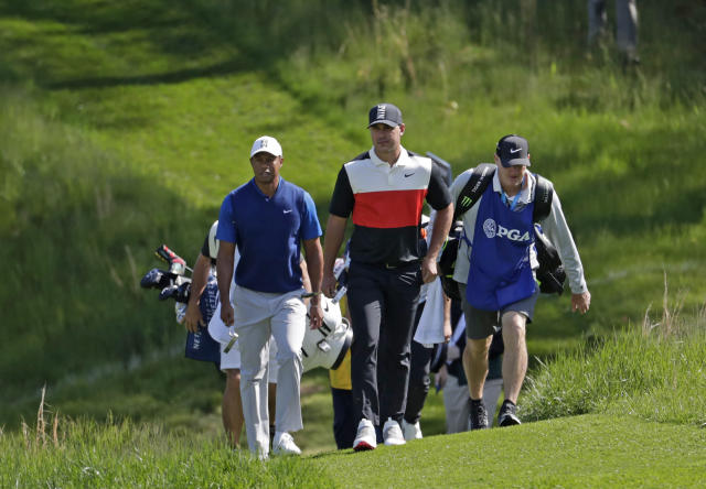 Tiger Woods, left, and Brooks Koepka walk to the 14th fairway during the first round of the PGA Championship golf tournament, Thursday, May 16, 2019, at Bethpage Black in Farmingdale, N.Y. (AP Photo/Julio Cortez)