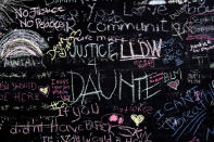 FILE - This April 22, 2021 file photo shows a chalkboard near a makeshift memorial in Brooklyn Center, Minn., near the site of the fatal shooting of Daunte Wright by a police officer during a traffic stop. Minnesota Attorney General Keith Ellison says his office will lead the prosecution of former Brooklyn Center Officer Kim Potter who is charged with second-degree manslaughter in the death of Daunte Wright. Potter, who is white, fatally shot Wright, a 20-year-old Black motorist, on April 11, 2021. (AP Photo/Morry Gash, File)