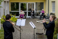 FILE - In this April 13, 2020 file photo, young musicians plays the trumpet, right, and trombone in the garden of a retirement and nursing home in Karben near Frankfurt, Germany. They played various pieces for the old people who are due to the coronavirus not allowed to leave the building. More than 50,000 people have died after contracting COVID-19 in Germany, a number that has risen swiftly over recent weeks as the country has struggled to bring down infection figures. (AP Photo/Michael Probst, File)