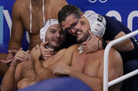 Greece assistant coach Dimitris Kravaritis hugs Christodoulos Kolomvos, left, and Konstantinos Mourikis (9) in the final moments of a win over Montenegro in a quarterfinal round men's water polo match at the 2020 Summer Olympics, Wednesday, Aug. 4, 2021, in Tokyo, Japan. (AP Photo/Mark Humphrey)