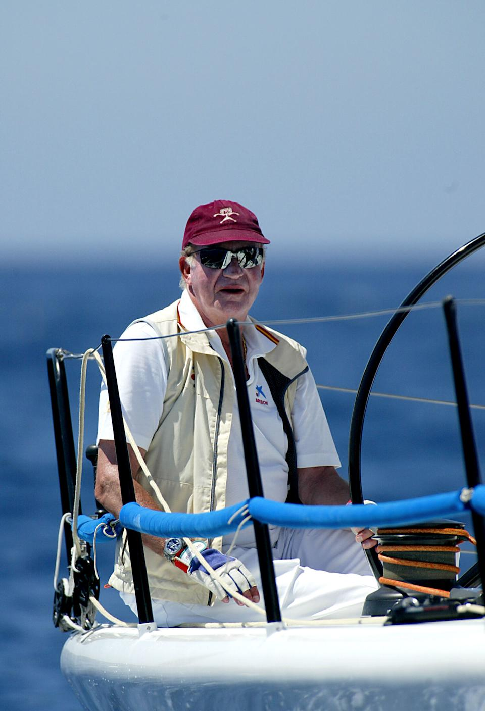"""Spain's King Juan Carlos is seen at the helm of the yacht """"Bribon"""" during the second Breitling regatta off the coast of Palma de Mallorca, 21 July 2006. The Spanish Royal Family are in Palma de Mallorca for their traditional summer holidays at the Marivent Palace. AFP PHOTO/Jaime REINA (Photo by Jaime REINA / AFP) (Photo by JAIME REINA/AFP via Getty Images)"""