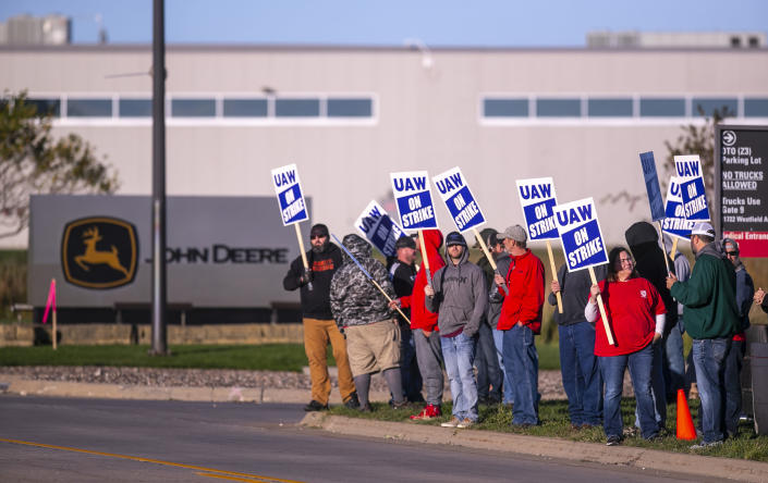 """John Deere Drivetrain Operations workers in Waterloo, Iowa, stand on the picket line at the plant as the UAW officially started its strike on Thursday, Oct. 14, 2021. More than 10,000 Deere & Co. workers went on strike Thursday after the United Auto Workers union said negotiators couldn't deliver a new agreement that would meet the """"demands and needs"""" of workers. (Chris Zoeller/The Courier via AP)"""