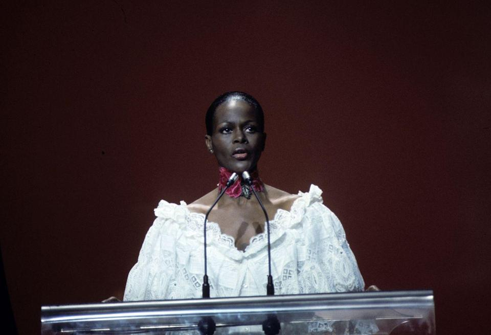 <p>Cicely presents at the 49th Academy awards in an off-the-shoulder-white billowy blouse and red choker, adding a playful element to her regal presence. </p>