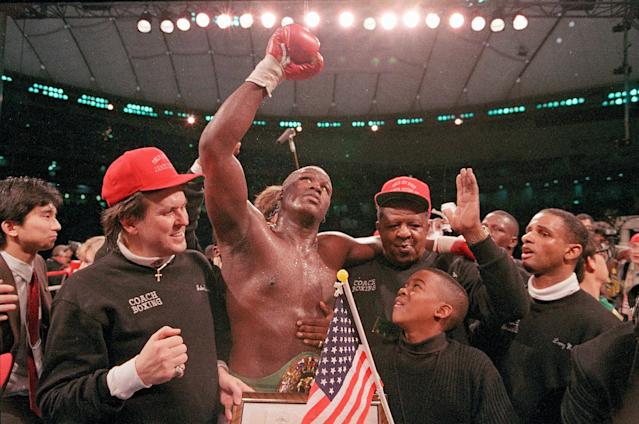"""FILE - In this Feb. 11, 1990, file photo, heavyweight boxer James """"Buster"""" Douglas waves his gloved hand to the cheering crowd as he makes his way to the dressing room following a 10th round knockout victory over Mike Tyson in a scheduled 12-round championship bout at the Tokyo Dome. In one of the more spectacular upsets in sports history, Douglas defeated Tyson, the reigning world heavyweight champion on Feb. 11, 1990, in Tokyo. (AP Photo/Sadayuki Mikami, File)"""
