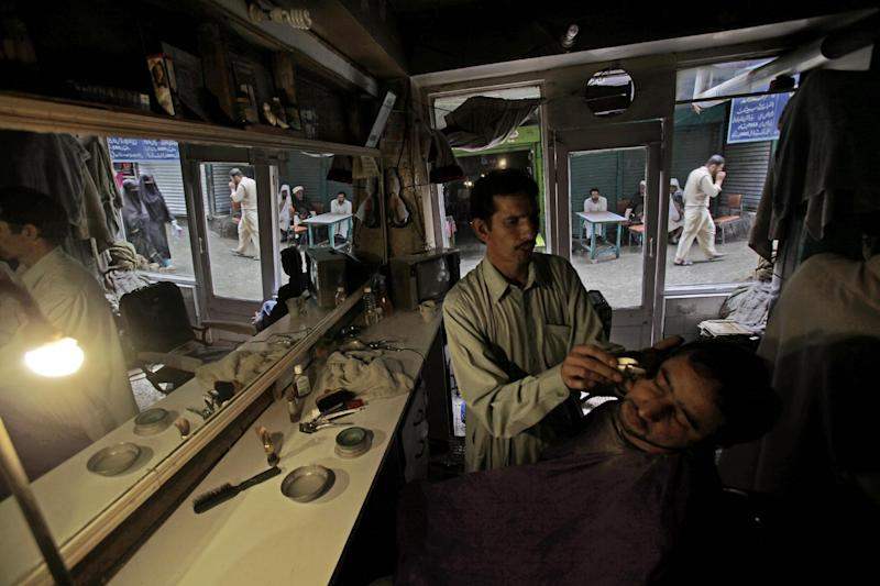 In this Sunday, April 29, 2012 photo, Pakistani barber Mohammed Arif, 35, lights his shop with a lamp due to a power cut, while shaving a customer, in Abbottabad, Pakistan. One year since U.S. commandos flew into this army town and killed Osama bin Laden, Pakistan has tried to close one of the most notorious chapters in its history. The compound that housed him for six years was razed to the ground, and the wives and children who shared the hideaway were flown to Saudi Arabia just last week. (AP Photo/Muhammed Muheisen)
