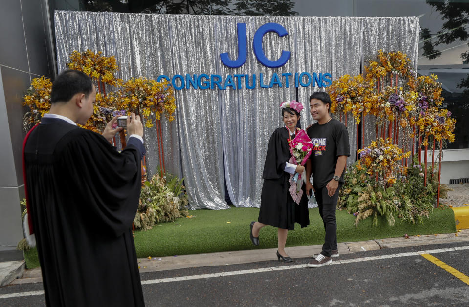 A university student poses for a photo ahead of a graduation ceremony at the Thammasat University, Friday, Oct. 30, 2020, Bangkok, Thailand. (AP Photo/Sakchai Lalit)