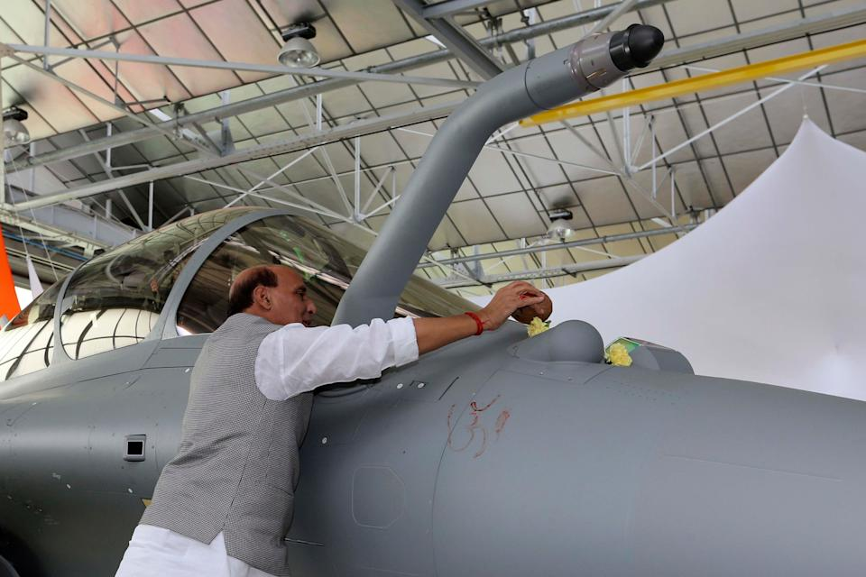 Defense Minister Rajnath Singh put some flowers as a ritual gesture on a Rafale jet fighter during an handover cermony at the Dassault Aviation plant in Merignac, near Bordeaux, southwestern France, on 8 October.