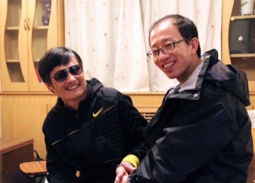 Outspoken government critic Hu Jia (R) sharing a light moment with blind lawyer Chen Guangcheng after his escape