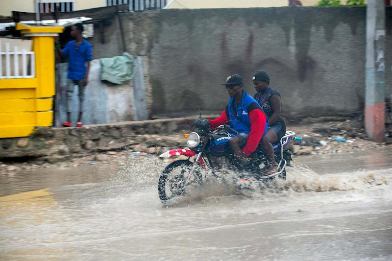A moto-taxi driver moves through a flooded street during the beginnings Hurricane Isaias in Port-au-Prince, Haiti (AP)