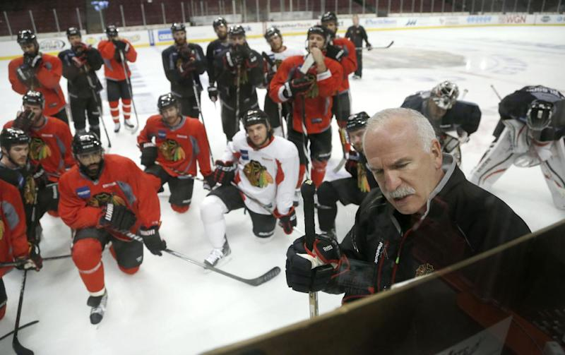 Chicago Blackhawks head coach Joel Quenneville, right, diagrams a drill during an NHL hockey practice Friday, June 21, 2013 in Chicago. The Blackhawks will host the Boston Bruins in Game 5 of the Stanley Cup Final series Saturday. (AP Photo/Charles Rex Arbogast)