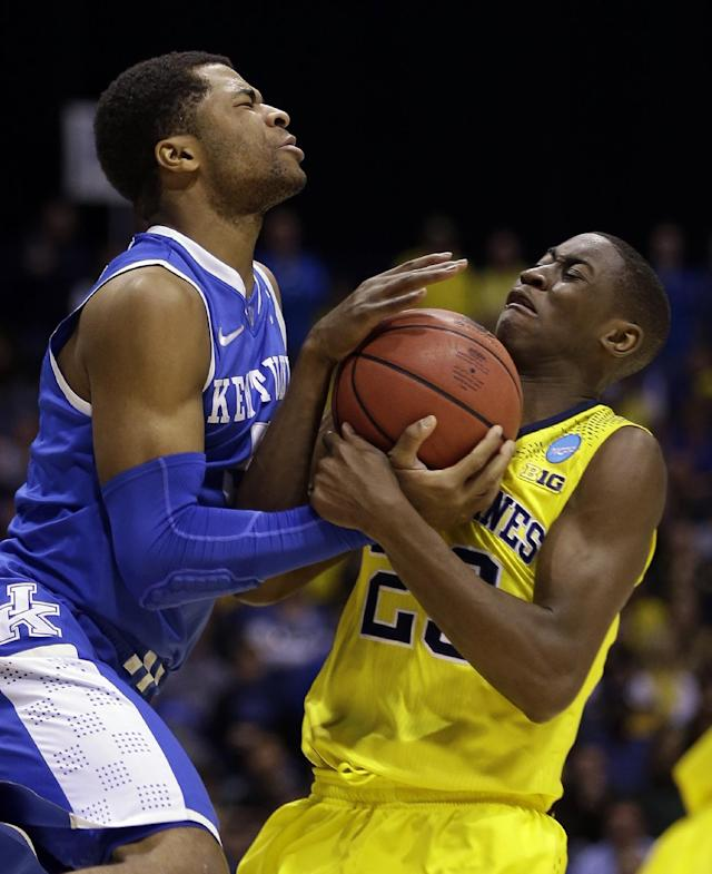 Kentucky's Andrew Harrison and Michigan's Caris LeVert go after a loose ball during the second half of an NCAA Midwest Regional final college basketball tournament game Sunday, March 30, 2014, in Indianapolis. (AP Photo/David J. Phillip)