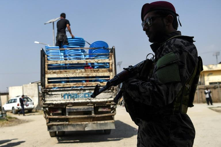 A security personnel in Kabul stands guard on September 29, 2019 as Independent Election Commission (IEC) workers unload ballot boxes to be taken to a counting centre the day after Afghanistan held its presidential election