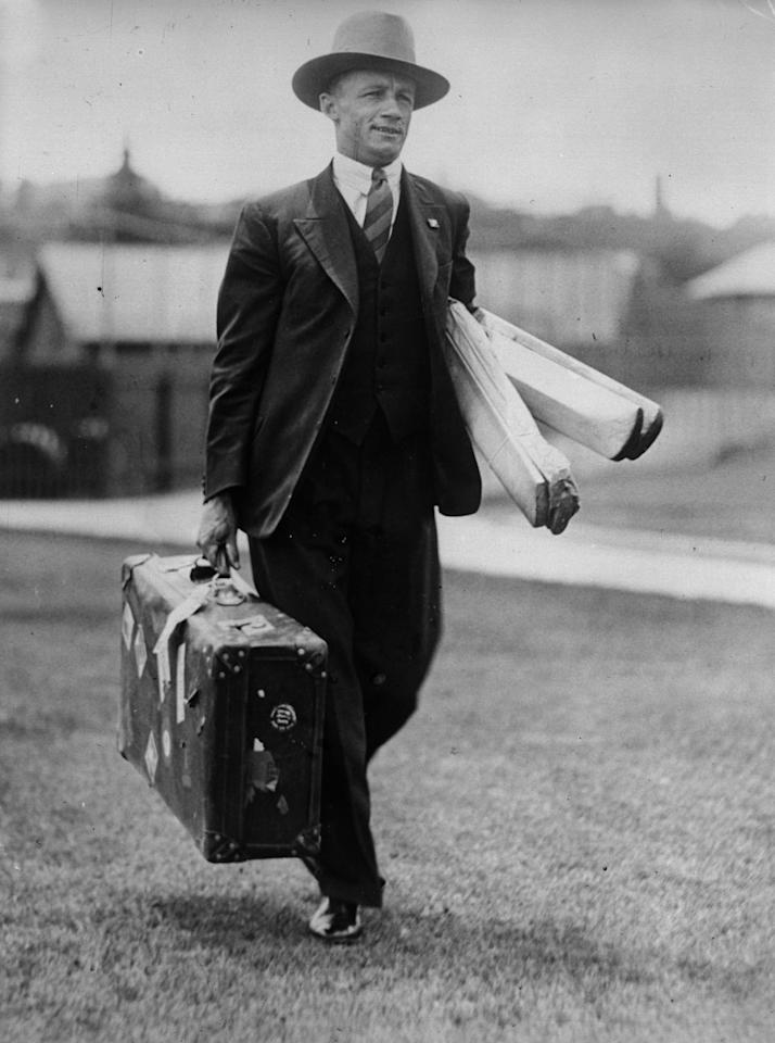 1932:  Australian cricketer Donald Bradman (1908 - 2001) arrives for an important match carrying his suitcase and bats.  (Photo by Fox Photos/Getty Images)