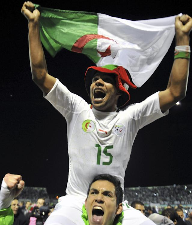 Algeria's El Arabi Soudani, top, holds a flag of Algeria as he celebrates the victory with his teammate Aissa Mandi during their World Cup qualifying soccer match against Burkina Faso in Blida, Algerias, Tuesday, Nov. 19, 2013. Algeria claimed Africa's final place at the World Cup on away goals after edging Burkina Faso 1-0 in the second leg of their playoff on Tuesday. (AP Photo/ Anis Belghoul)