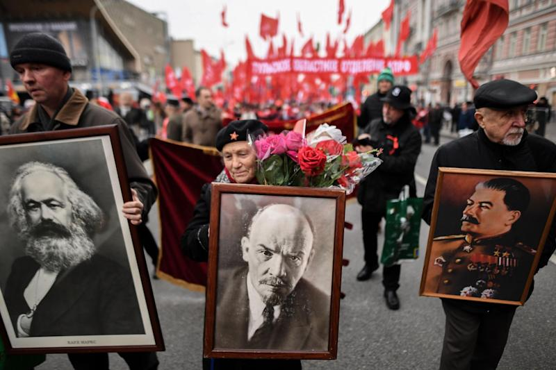 Russian Communist supporters holding portraits of Karl Marx, Vladimir Lenin and Joseph Stalin participate in a rally marking the 100th anniversary of the 1917 Bolshevik Revolution in downtown Moscow on November 7, 2017. / AFP PHOTO / Kirill KUDRYAVTSEV (Photo credit should read KIRILL KUDRYAVTSEV/AFP via Getty Images): Getty