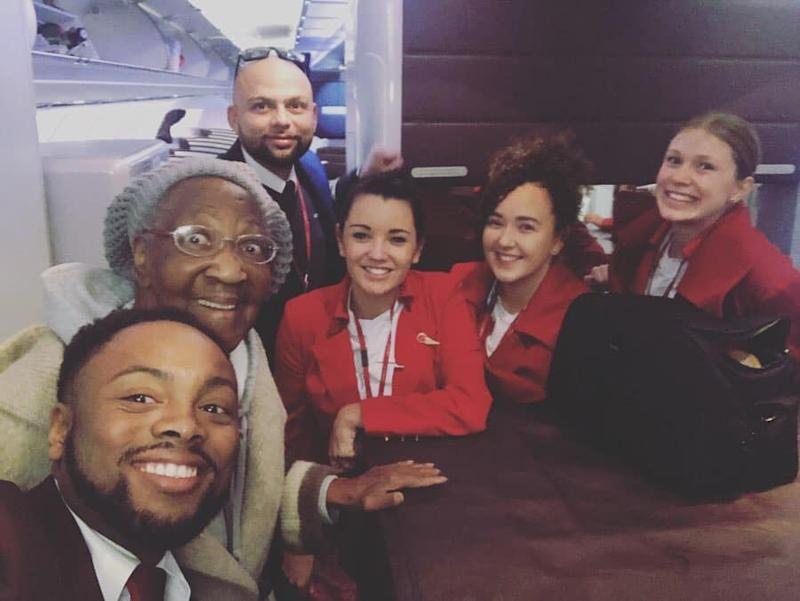 Virgin Atlantic flight staff pictured with passenger Violet who sat first class after a stranger gave her his seat.