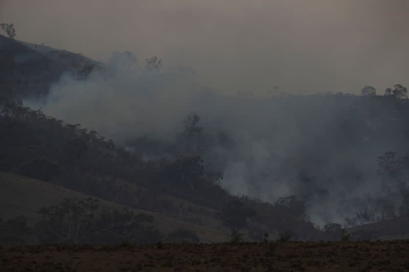 Smoke rises from the smouldering remnants of a bushfire near Bumbalong