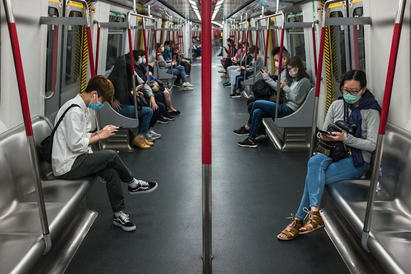 TOPSHOT - People wearing face masks, amid concerns of the COVID-19 coronavirus, commute on a train in Hong Kong on April 4, 2020. (Photo by DALE DE LA REY / AFP) (Photo by DALE DE LA REY/AFP via Getty Images)