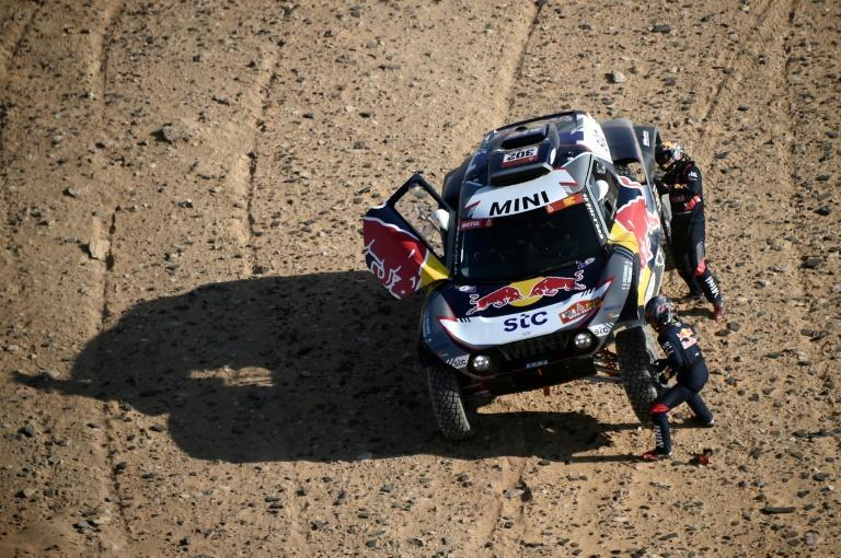 Mini driver Stephane Peterhansel and his co-driver Edouard Boulanger of France change a tyre
