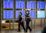 German police officers wearing face mask walk past a flight board in a terminal at the airport in Frankfurt, Germany, Tuesday, May 11, 2021. Flight numbers went down after the outspread of the corona virus. (AP Photo/Michael Probst)